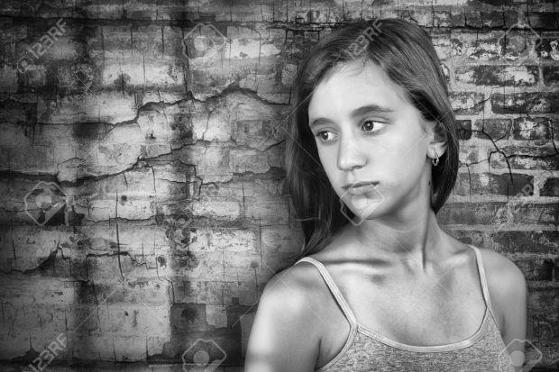 41118096-triste-et-solitaire-adolescente-debout-à-côté-d-39-un-mur-de-briques-grunge-Banque-d'images.jpg